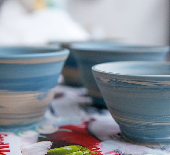 Ceramic bowls in various stages of being painted blue. Photo credit: Libby Kamrowski