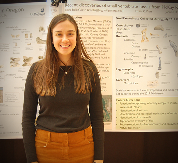 Female student stands proudly in front of her research project board.