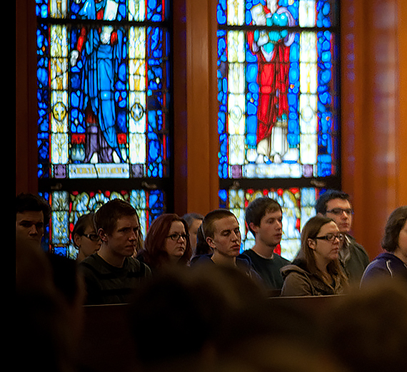 Students listen to a lecture. Stained glass is the background.