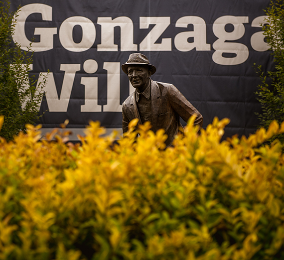 Statue of Bing Crosby behind fall yellow leaves. Gonzaga Will banner drapes the background.