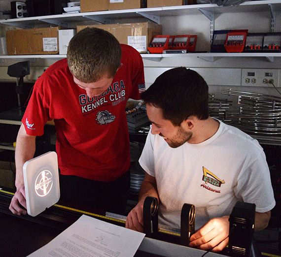 Two physics students filter a beam of light for a project