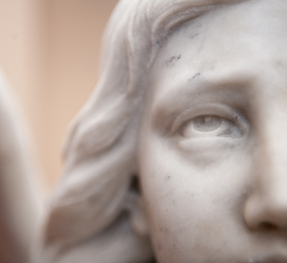 A statue of an angel looks up outside of St. Aloysius.