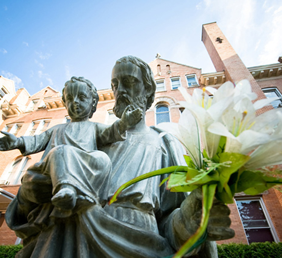 The Statue of St. Joseph holding an infant Jesus Christ in the foreground of College Hall.
