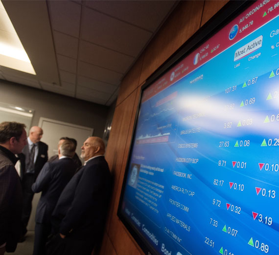 Stock market screen in crowded room.