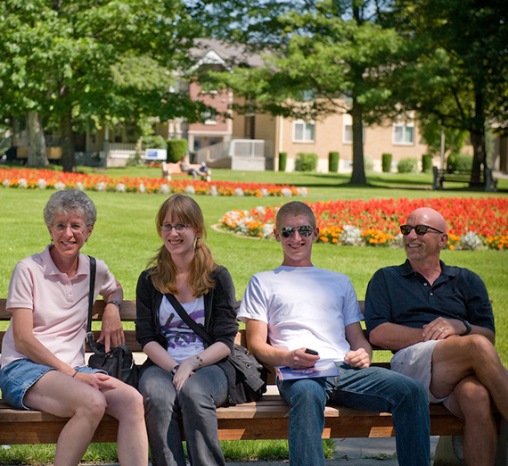 A Gonzaga family sitting on a bench on campus