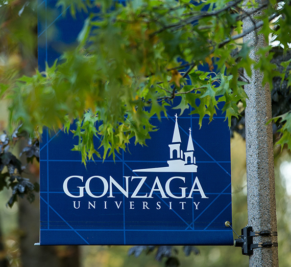 A blue Gonzaga post banner behind green tree leaves