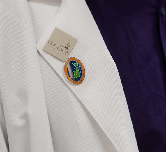 Pins signifying the Regional Health Partnership on a white lab coat.