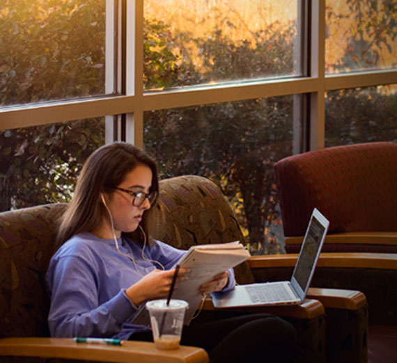 Undergraduate business student studying in Jepson Center lounge