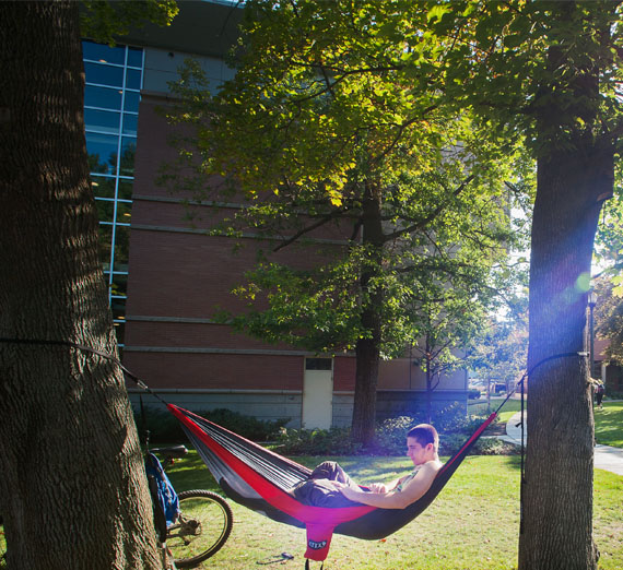 student laying in hammock on campus