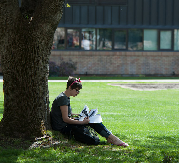 Student sitting by a tree on Herak lawn.
