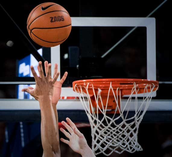 Outstretched arms of a Gonzaga basketball player going for a rebound near the hoop.