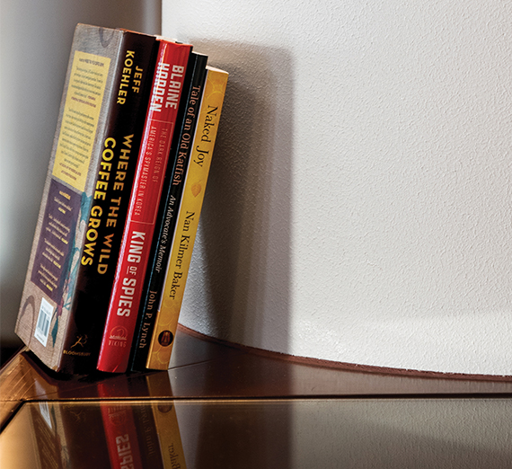 A collection of prose books leans against a column