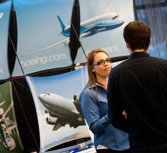 student talking to recruits from Boeing at career fair