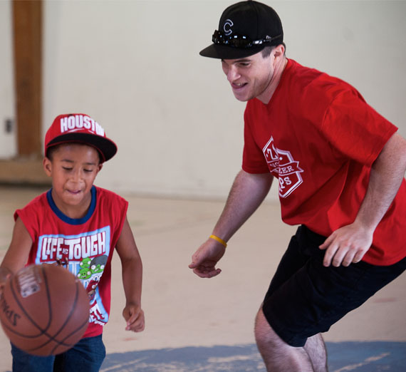volunteer playing basketball with kids