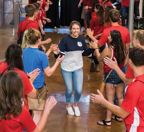 GU student runs through a tunnel of students giving her a high-five