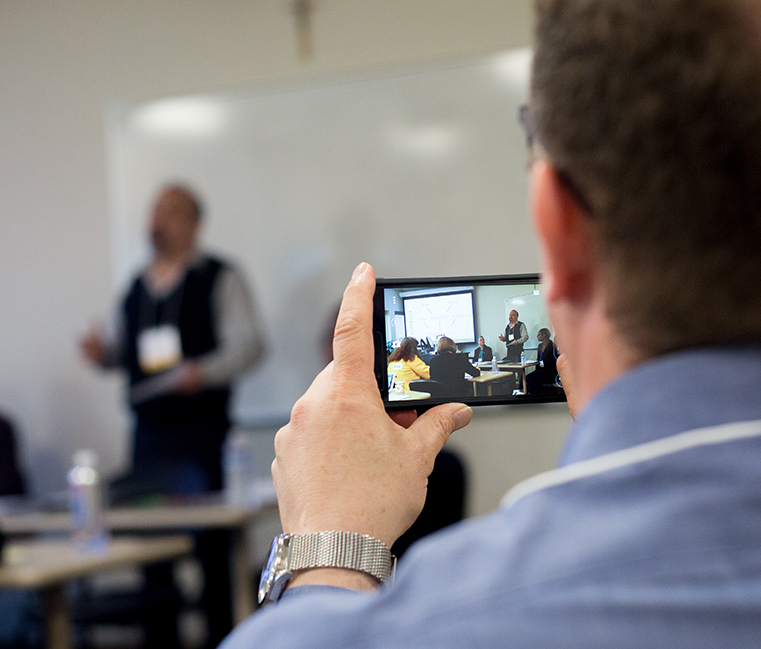 A student is videotaped while giving a presentation.