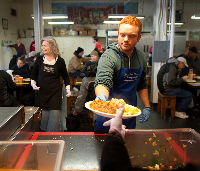 A student participates in Mission Possible in Portland by serving at a food kitchen