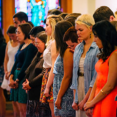 Students standing together in prayer.
