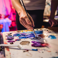 A student uses a paintbrush to mix colors