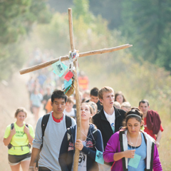 Students carry a wood cross as they walk on a trail in the forest