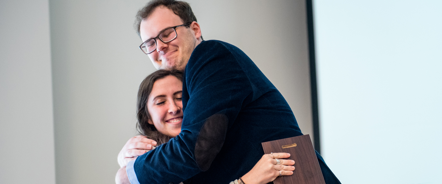 Two students hug after receiving a magis award