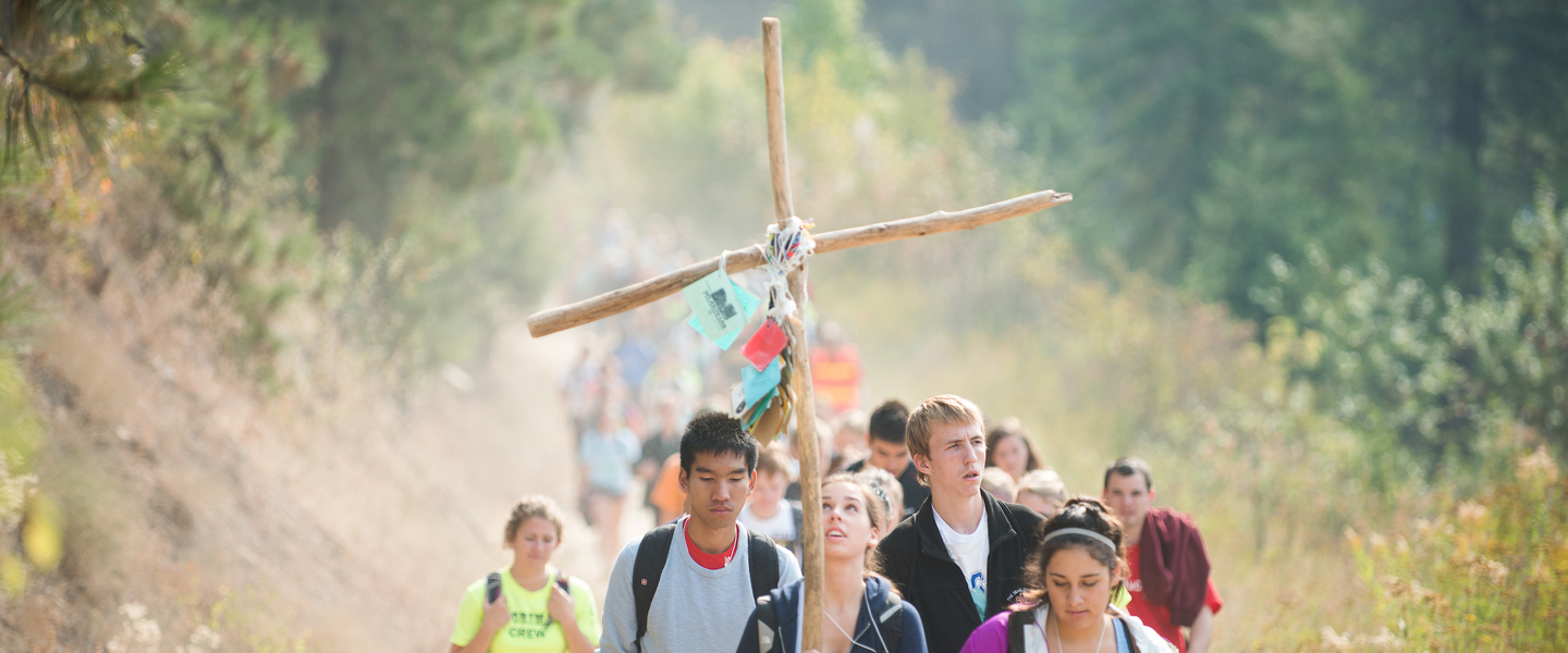 Students walk in a line behind the leader carrying a cross