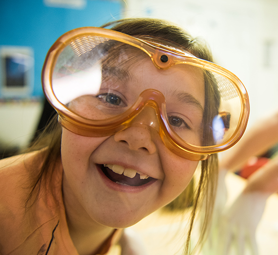 A child wearing safety goggles smiles into the camera
