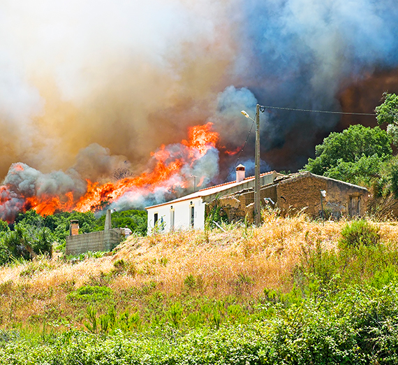 A wildfire rages behind a home near a wooded area