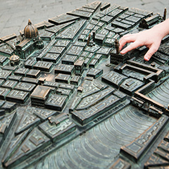 A student touches a building on a bronze 3D map of Florence