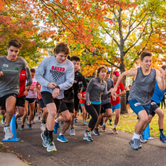 Students begin a 3k race under golden autumn trees