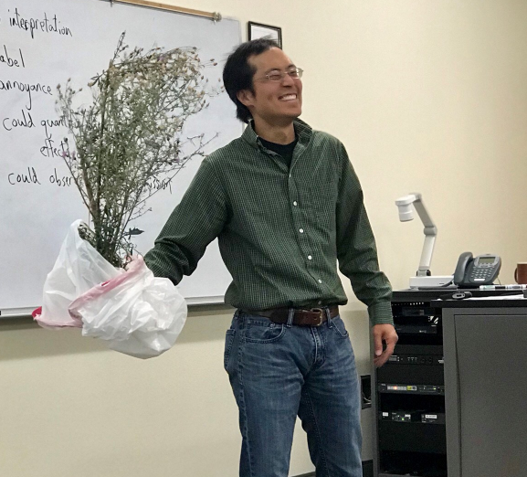 Professor Chang holds a tree in front of the classroom