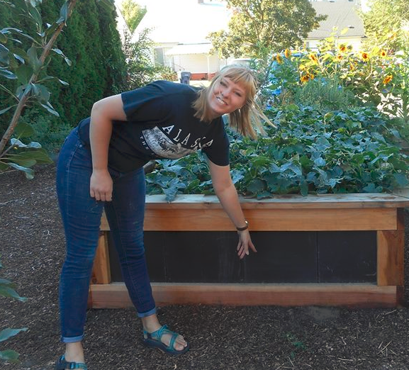 Carrie Herrman pointing to a plant at the Campus Garden