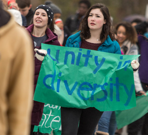 "Student with sign at diversity march that says ""unity in diversity"""
