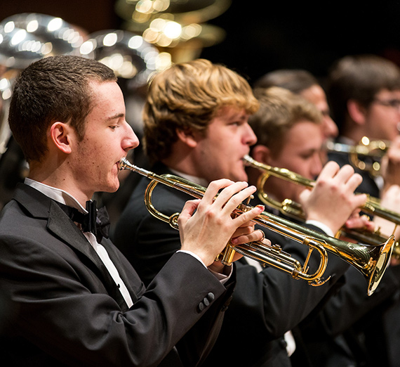 Members of the brass section of the Wind Symphony rehearse for a concert