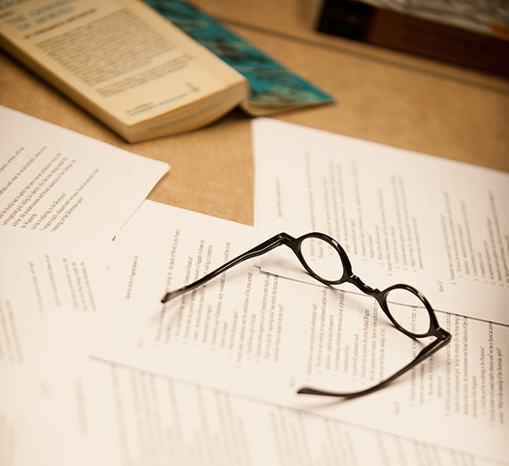 A pair of glasses rests on a pile of papers near an open book on a table