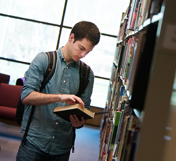 Student standing in the library reading