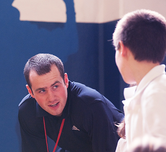 A coach speaks with a student