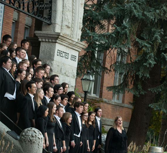 choir singing on steps of college hall