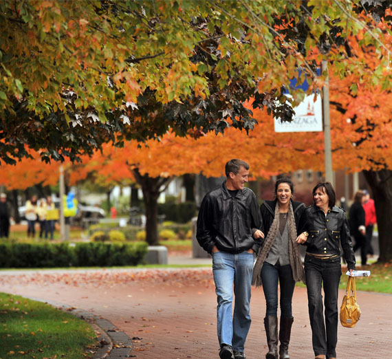 student walks with parents on campus