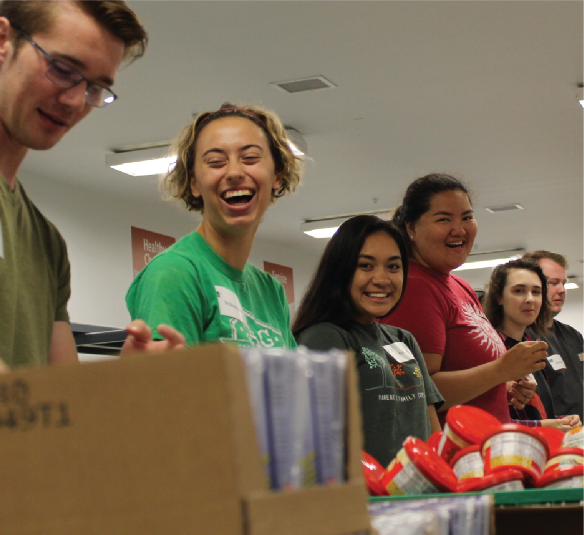 Students laughing as they pack food at Second Harvest Food Bank