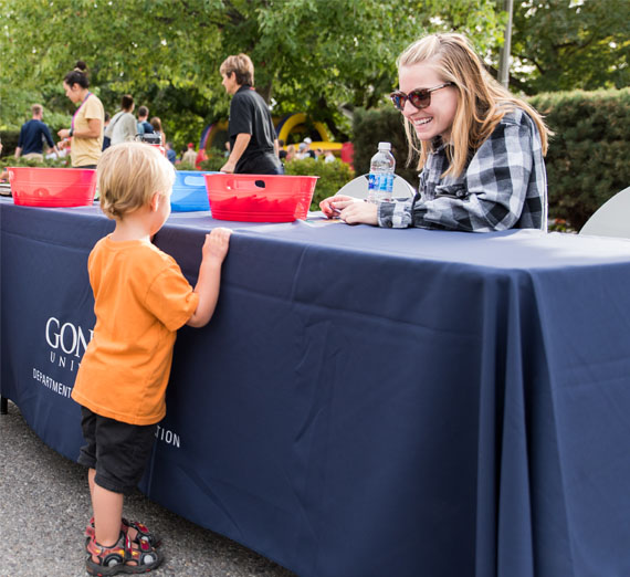 volunteer with child at block party