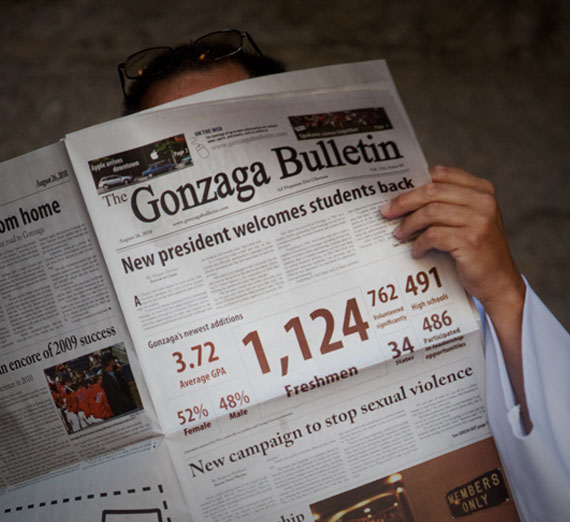 Priest reading the Gonzaga Bulletin student newspaper
