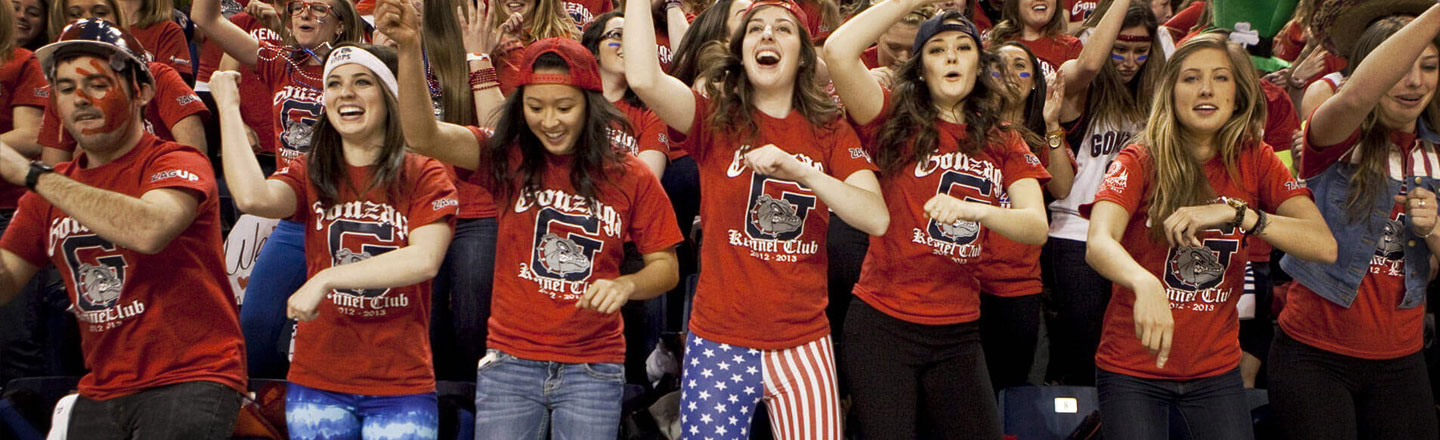 Students cheering in Gonzaga's Kennel Club section at a basketball game