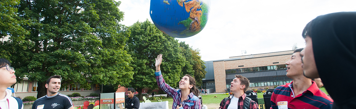 international students at the Welcome Back celebration tossing an inflateable globe into the air