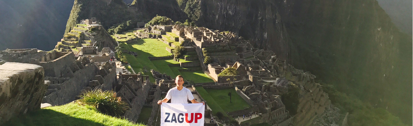 A Gonzaga student holding a ZagUp flag at Machu Picchu. Photo by Mason Matteoni