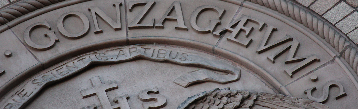 Metal casting of Gonzaga written in latin. Partial image of larger round casting set on side of a building.