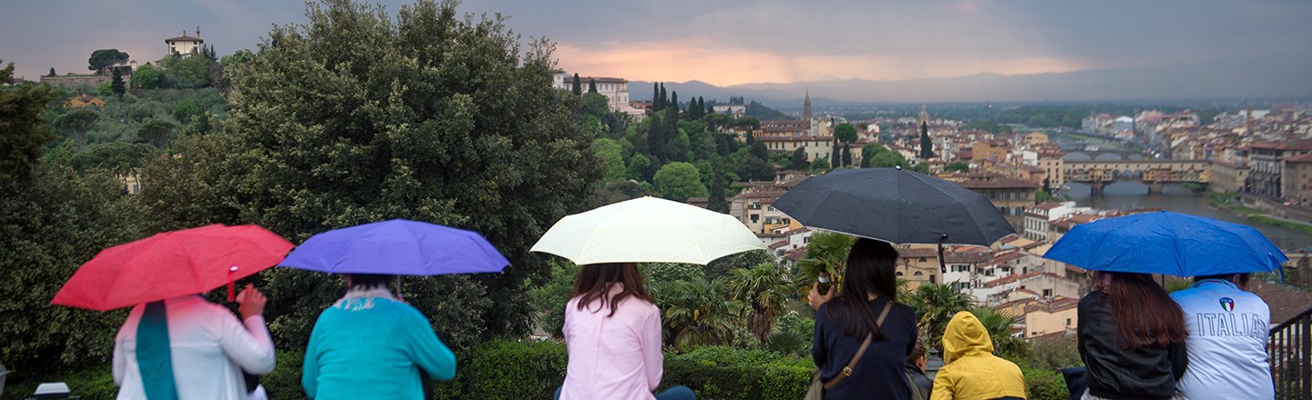Gonzaga University Italian Studies students with umbrellas looking over an Italian city