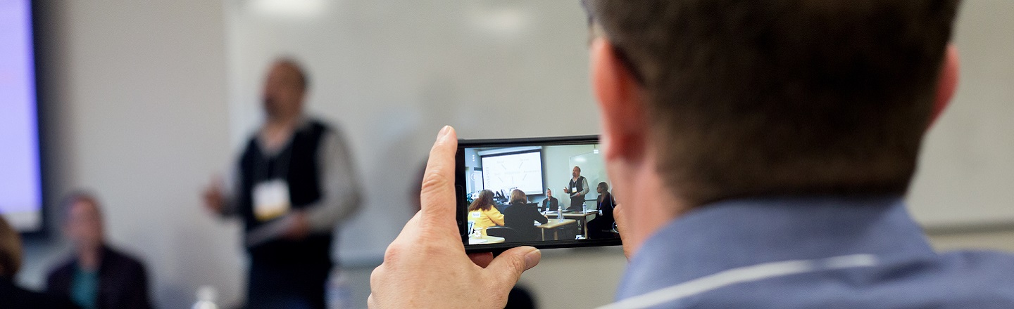 An audience member takes a photo with a smartphone during a presentation.