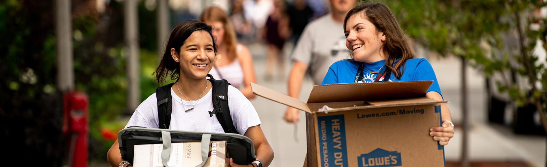 two students carrying boxes