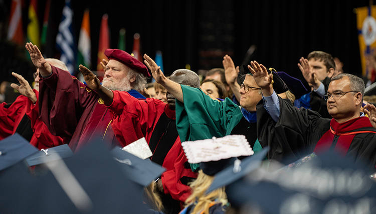 jesuits and professors raise hands to bless graduates